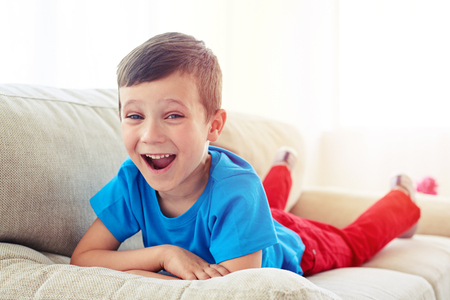 Close-up shot of surprised small boy lying on the sofa. Small child relaxing on the settee in the living room