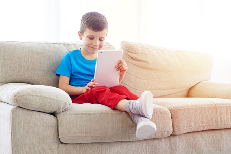 concentrate: Close-up shot of smiling boy with tablet relaxing on the sofa. Little kid holding electronic tablet while sitting on the settee