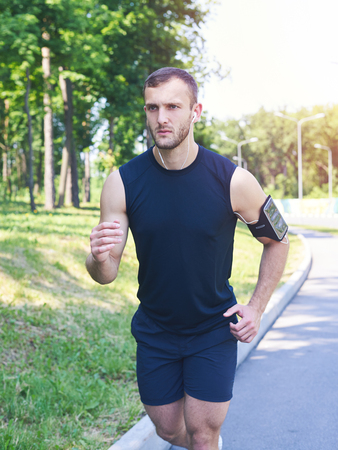 Vertical of good-looking man running in park while listening to music Stock Photo