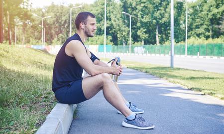 Mediados de disparo un hombre serio llevaba paño deportivo, sentado en el bordillo de la calle, la celebración de una botella de agua