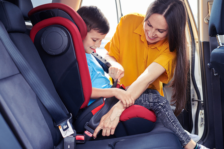 Wide shot of gorgeous mom helping son sitting in baby seat to fasten seat belt Stock Photo