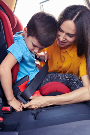 Vertical of caring mother helping son sitting in baby seat to fasten seat belt photo