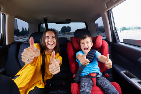Mid shot of a mother and her child, both buckled the seat belt. Family holding their thumbs up, having fun together photo