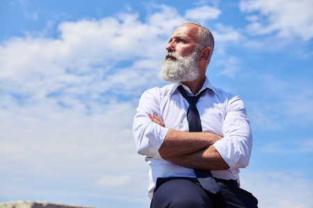 Mid shot of elderly bearded man having his arms folded, wearing white shirt; sitting and looking aside