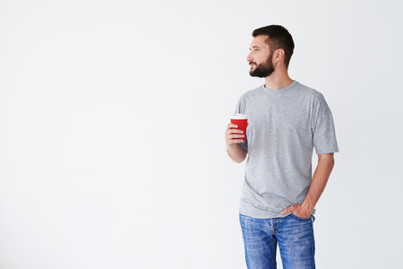 hands in pocket: Bearded man in front of white background, narrowing eyes, holding carton cup, wearing casual cloth, mid shot