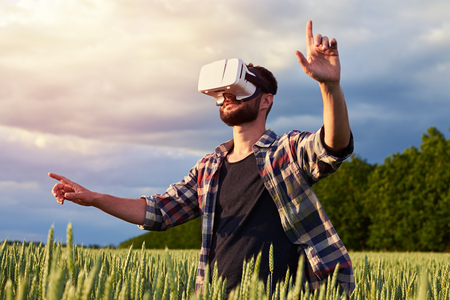 virtual reality simulator: Side view from below of man of middle age using 3D glasses surrounded by field of weed. Pointing with his fingers, mid shot Stock Photo