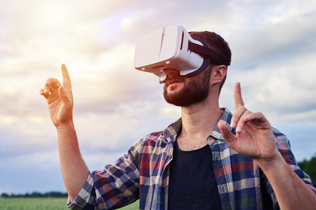 Close-up shot of middle-aged Caucasian bearded man using VR glasses while standing in the middle of green wheat field. Zooming object, virtual reality Stock Photo