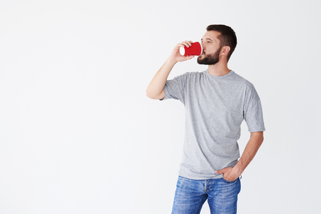 Man standing against white background and drinking red carton cup of coffee, one hand in pocket, mid shot