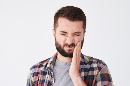 he: Close-up shot of sad bearded young man suffering from toothache. Man touch cheek. He have strong tooth ache Stock Photo