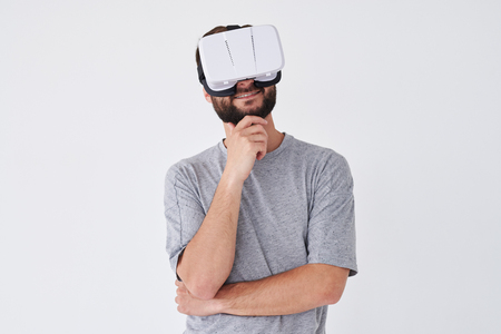 virtual reality simulator: Close-up shot of handsome bearded male using VRG making thinking gesture isolated on white background Stock Photo
