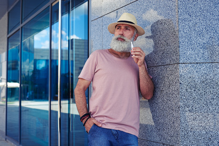 Mid shot of  bearded man with electro cigarette dressed in casual clothing, standing outdoors, narrowing eyes, holding hand in pocket Stock Photo