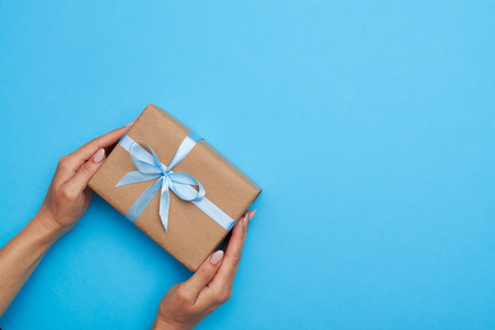 Top view of hands placing a wrapped box, tied with a ribbon. Gift box lying on blue background