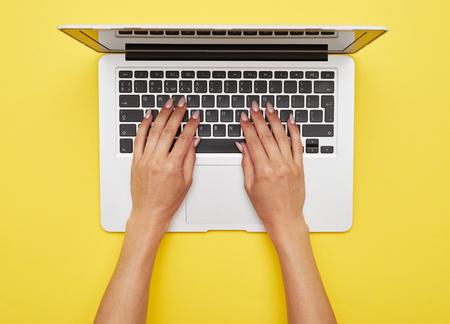 노란색 배경에 노트북 서에서 인쇄하는 여자 손의 평면 누워