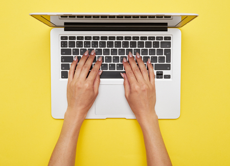 Flat lay of woman hands printing in laptop standing on yellow background