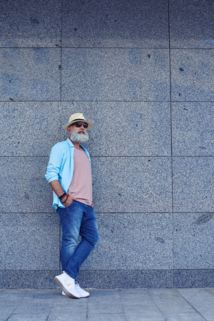 looking aside: Full-length portrait of man with grey beard in stylish clothing, wearing sunglasses and sneakers, mid shot