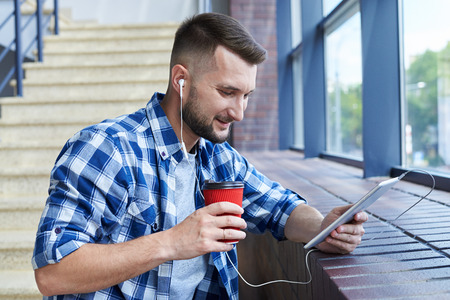 Side view of urban bearded man listening music while using tablet. Standing next to the window, holding tablet in hands Stock Photo