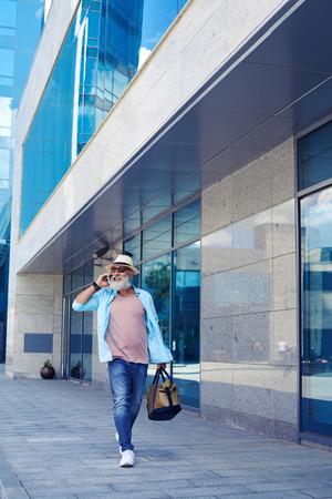 sidewalk talk: Vertical of fashionable old man talking on phone and walking down street while carrying handbag