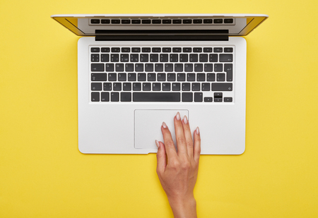 Flat lay of female hand using touchpad of laptop on yellow background Stock Photo