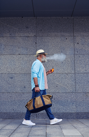 Man walking directly and smoking e-cigarette holding brown bag wearing sneakers and jeans, hat on head, side view, mid shot
