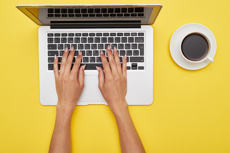Flat lay of workspace with woman hands printing in laptop and cup of coffee on yellow background