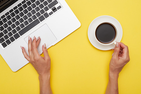 Flat lay of girl hands using touchpad and holding cup of coffee on yellow background