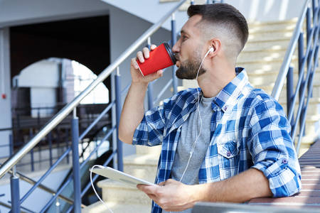 Close-up shot of bearded man with headphones listening to music on digital tablet, drinking coffee photo