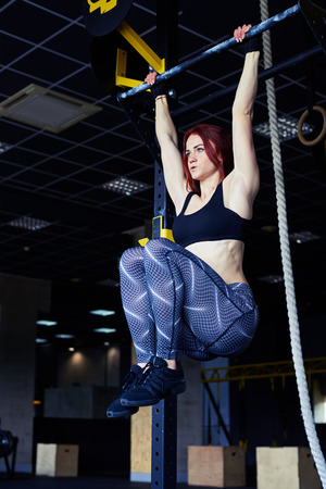 angle bar: Low angle of athletic woman training on horizontal bar in gym