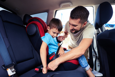 Close-up shot of concentrated father helping his son to fasten belt on car seat photo