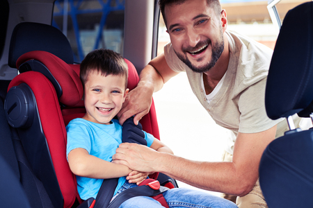 Close-up shot of happy father helping his son to fasten belt on car seat photo