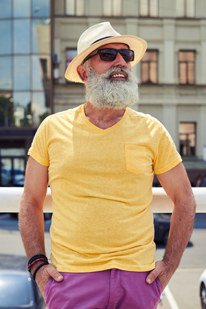 Close-up shot of stylish mature bearded man in bright yellow t-shirt and hat. Standing and leaning on handrail, looking at sky