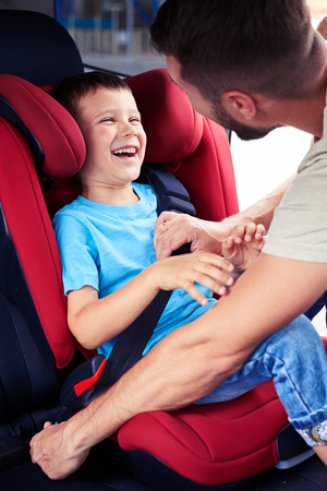Close-up shot of small boy smiling while his father helps to fasten belt on car seat photo