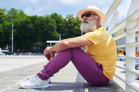 Close-up shot of old handsome bearded man leaning on his knees and holding his arms. Wearing sunglasses and straw hat photo