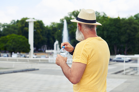 Rear view of man in straw hat holding plastic bottle of water with urban cityscape photo