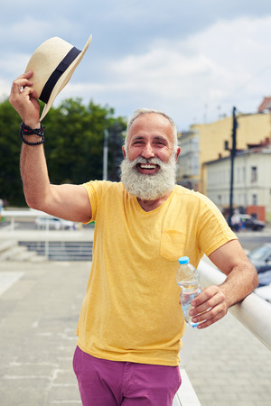 Mid shot of smiley bearded man taking off hat while standing with bottle of water photo