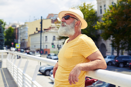 Side view of mature bearded man leaning on handrail while looking at sky. Enjoying beautiful panorama of city. Urban concept photo