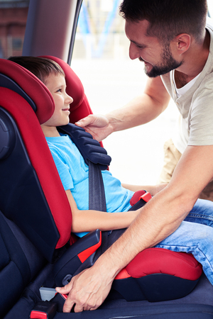 Side view of smiling son in infant car seat being put in back of car by caring father photo