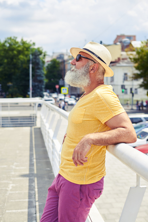 Side view of relaxed mature bearded man looking at sky. Leaning on handrail, enjoying city panorama photo