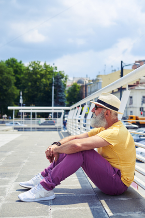 Side view of old handsome bearded man leaning on his knees and holding his arms. Wearing sunglasses and straw hat photo