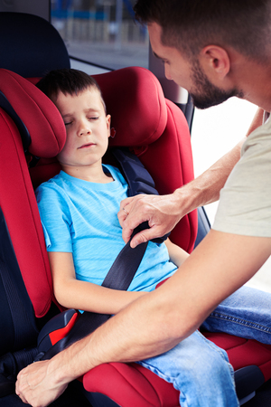 Side view of father helps his son to fasten belt on car seat while his son is sleeping photo