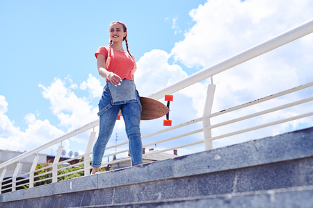 Low angle of good-looking female walking with skateboard in hands with copy space Stock Photo