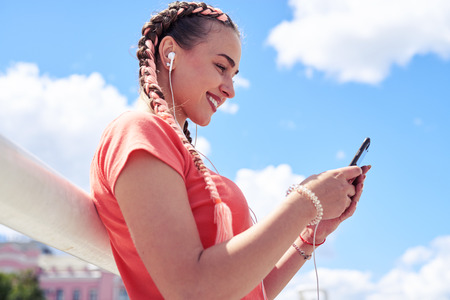 Low angle of stylish female in headphones surfing in smartphone