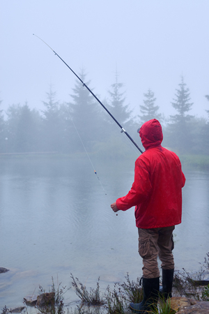 Side view of man in waterproof jacket fishing on rainy weather