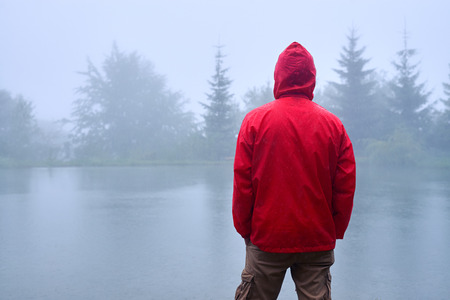 Rear view of man in waterproof jacket standing near lake and holding hands in pocket Stock Photo