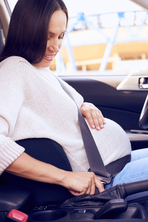 Side view of pregnant woman buckling up the seat belt before driving car