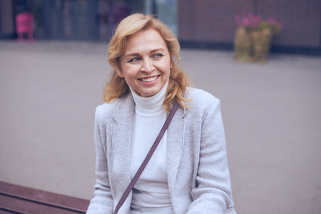 Closeup of smiling mature woman looking somewhere, sitting on bench outdoors