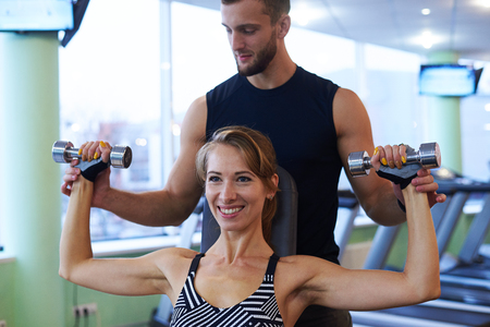 Closeup of smiling woman and personal trainer exercising in gym