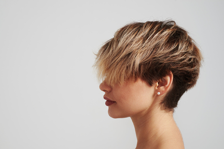 Portrait of beautiful blond woman with short hairstyle posing at studio