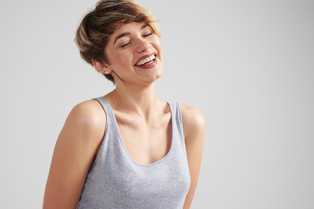Closeup shot of happy female laughing with closed eyes against white background