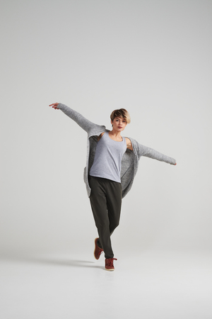 Full-length shot of happy young woman with arms outstretched
