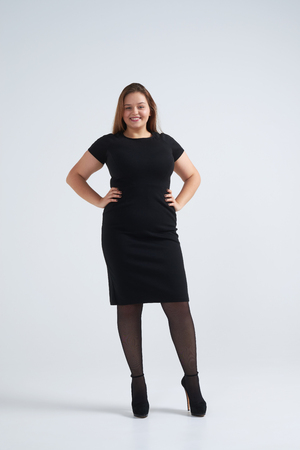 Full-length shot of smiling woman in classic black dress standing against background
